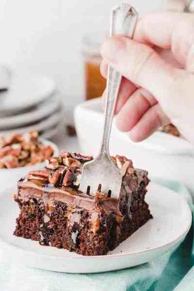 Chocolate turtle poke cake slice on plate dripping with chocolate sauce.