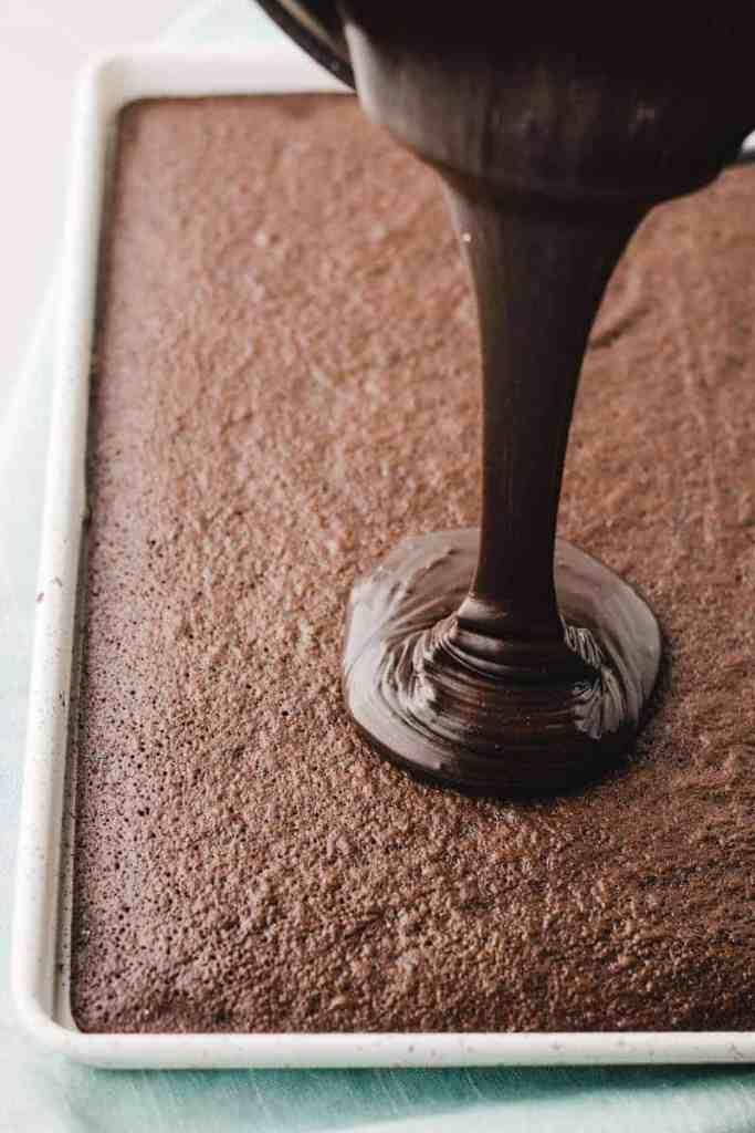 Warm chocolate icing poured onto warm chocolate sheet cake.