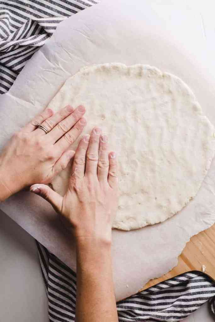 Patting out the pizza dough with rice flour