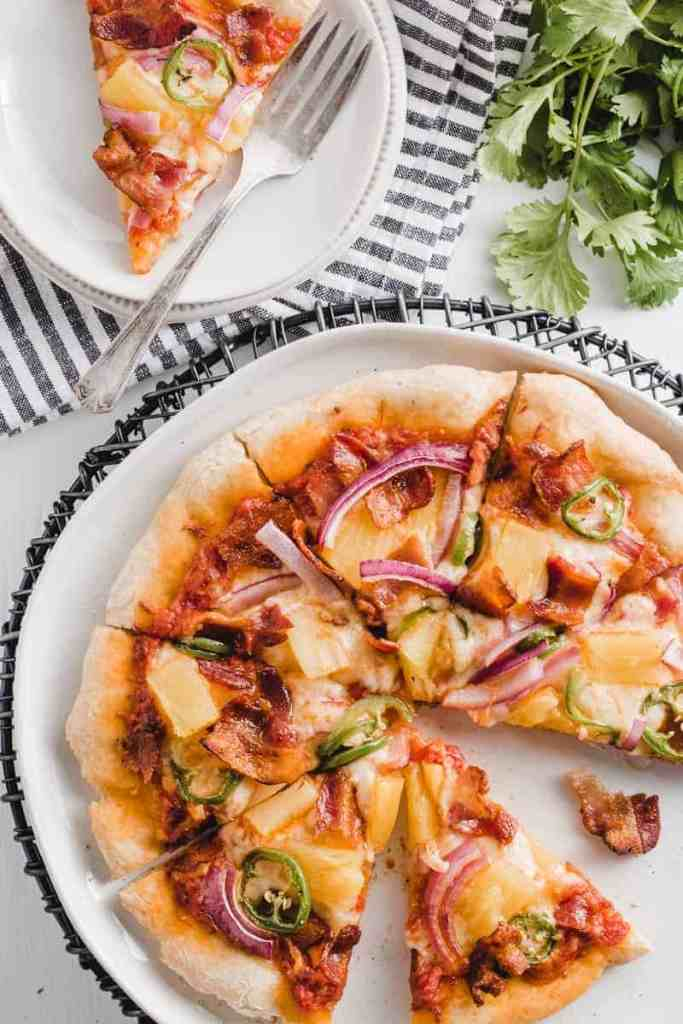 Sliced Spicy Hawaiian Bacon Pizza, one slice on a plate next to a vintage fork.