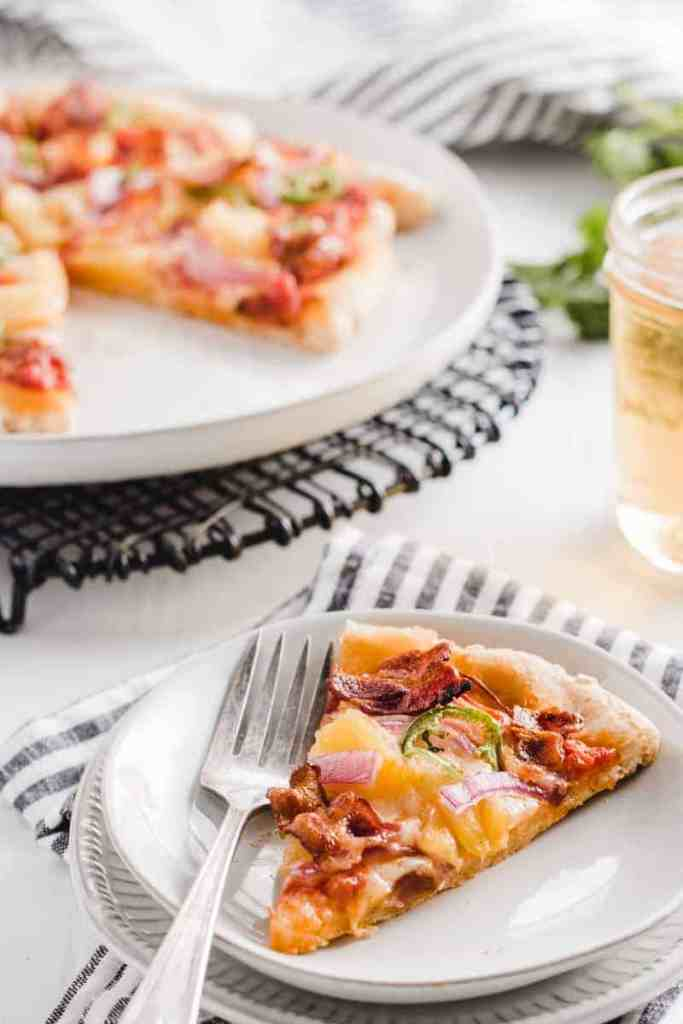 A slice of gluten-free spicy Hawaiian bacon pizza on a plate next to old fork. Rest of pizza on black wire trivet in background.