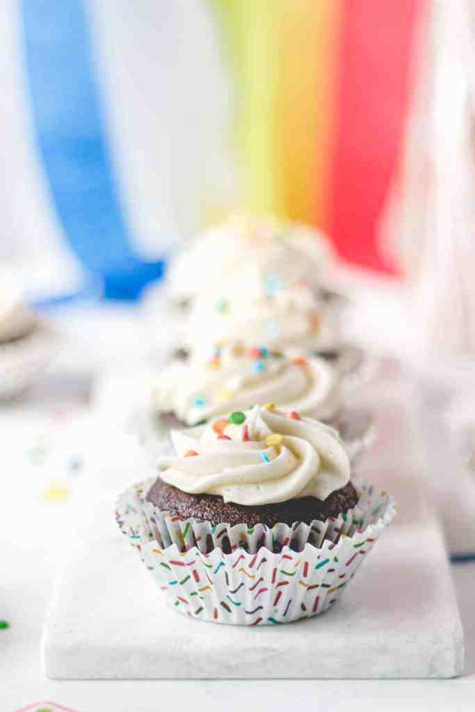 Gluten-free chocolate cupcakes with vanilla frosting and rainbow sprinkles in rainbow sprinkle cupcake wrappers.