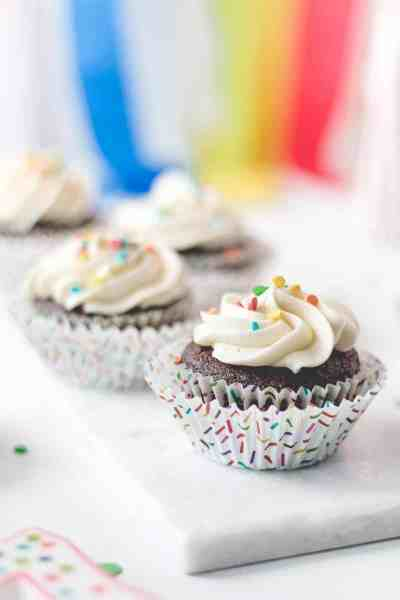 Gluten-free chocolate cupcakes with vanilla frosting in sprinkle cupcake wrappers.