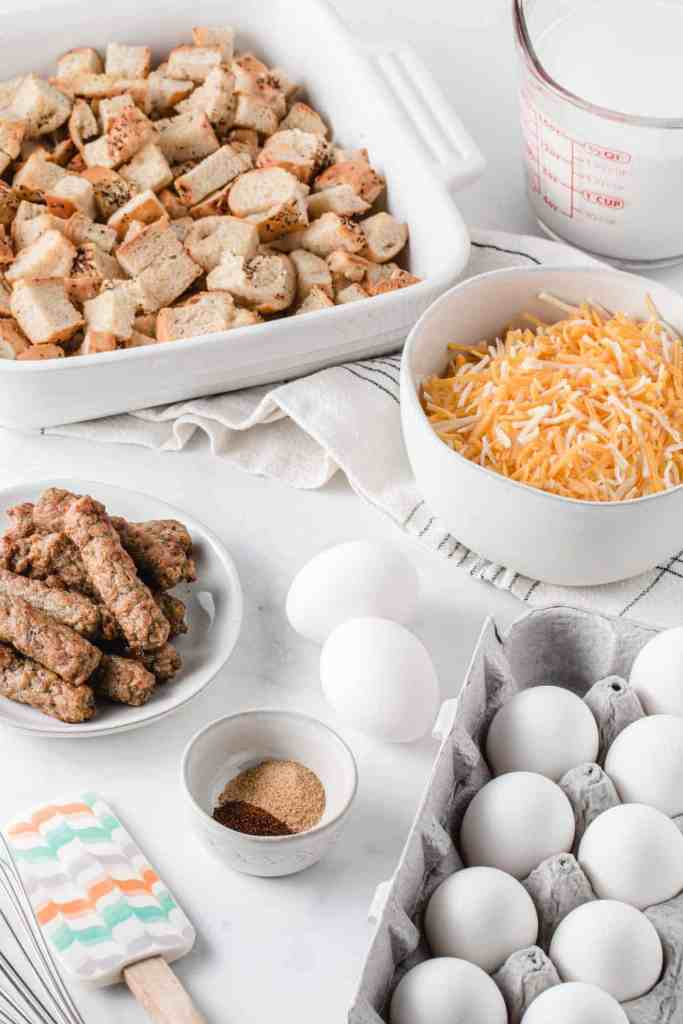 Ingredients for the breakfast casserole measured out in bowls, bread cubes in the baking dish.
