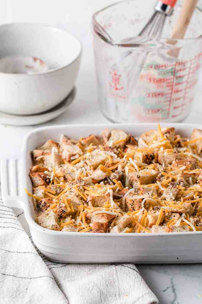 Unbaked bagel strata in baking dish with cheese sprinkled on top.