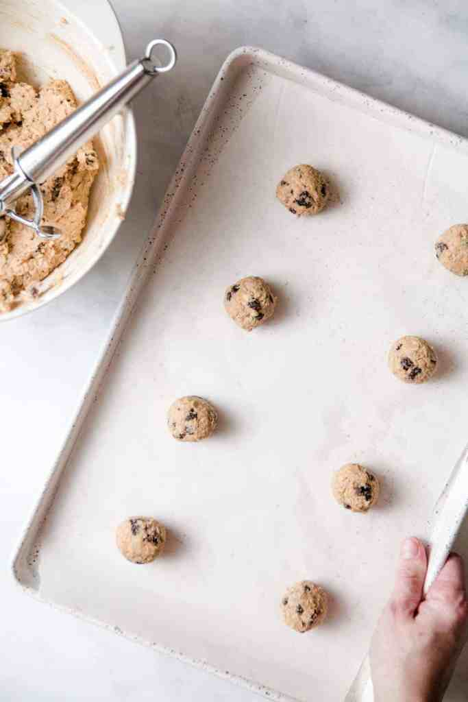 Rolled oatmeal cookie dough balls on a parchment lined baking sheet.