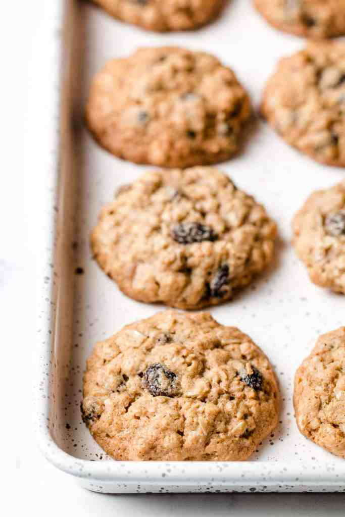 A batch of gluten-free oatmeal raisin cookies on a white speckled baking sheet.