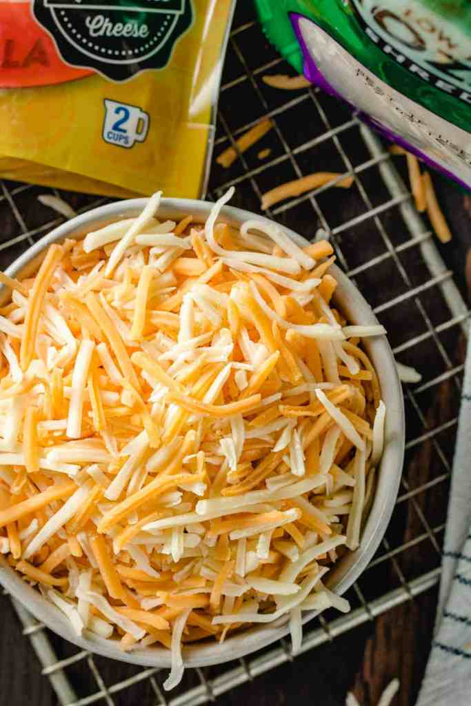 A bowl of pre-shredded cheddar-jack cheese on a brown table.