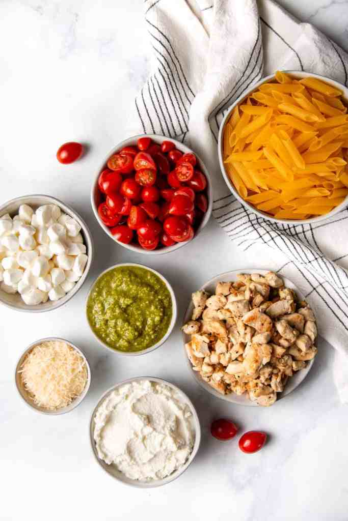 Ingredients for the chicken pesto pasta measured out in bowls including barilla gluten-free pasta.