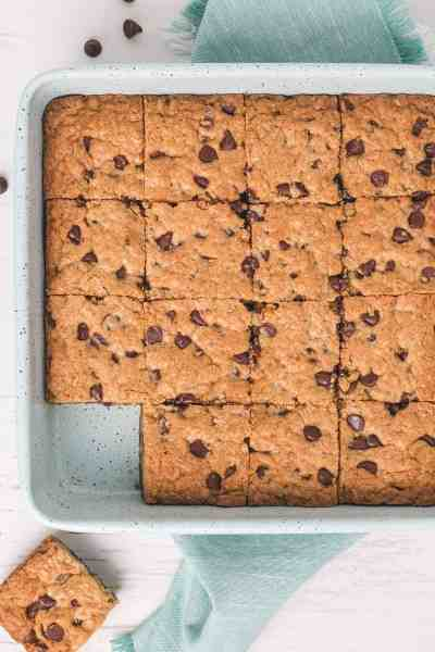 Gluten-free Oatmeal Chocolate Chip Bars in a blue square pan. One cookie off to the side.