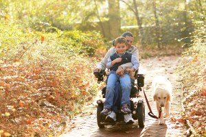 Dad in wheelchair going for walk with son