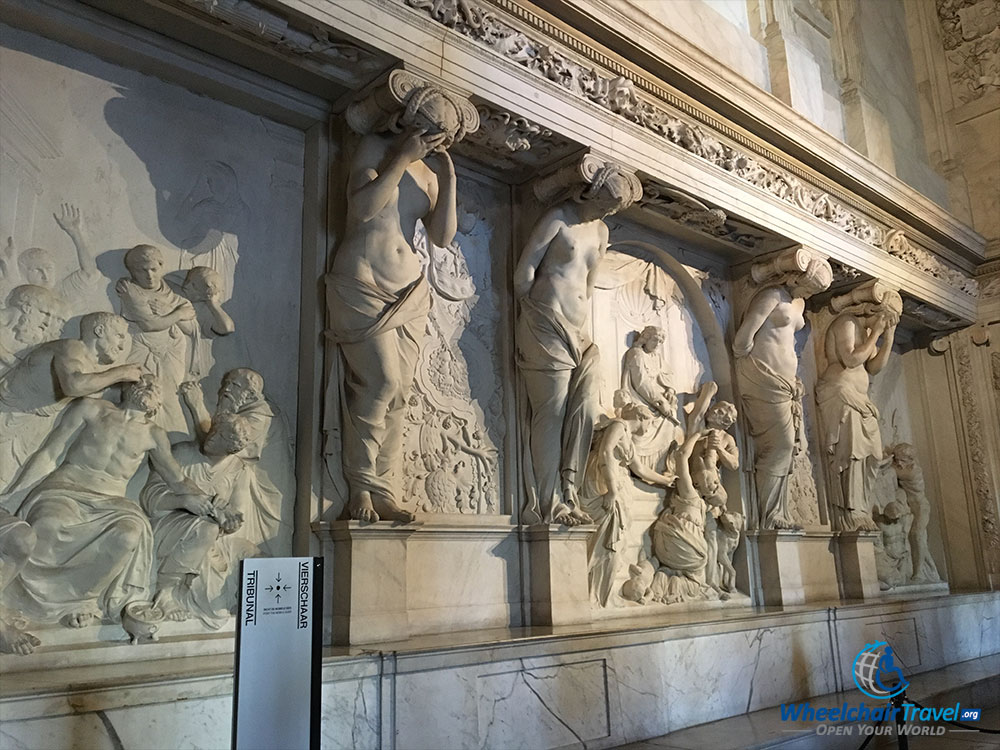 PHOTO DESCRIPTION: Four statue carvings laid into a wall, in what was the Town Hall's Tribunal.