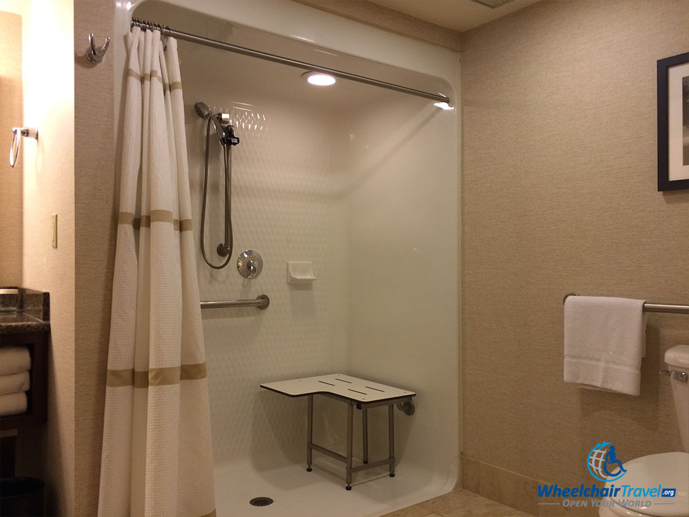 PHOTO DESCRIPTION: Wheelchair accessible roll-in shower with built-in shower bench, a handheld nozzle and a shower curtain.