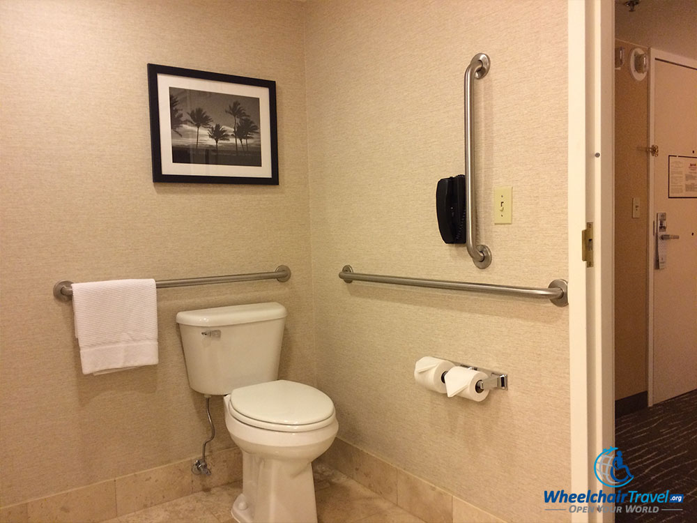 PHOTO DESCRIPTION: A wheelchair accessible bathroom toilet surrounded by grab bars.