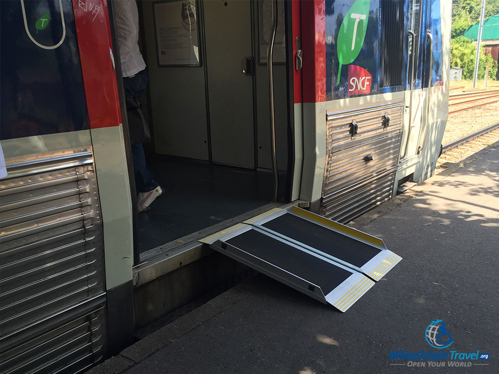 PHOTO DESCRIPTION: RER train at Versailles-Rive Droite Station with a wheelchair accessible ramp laid out.