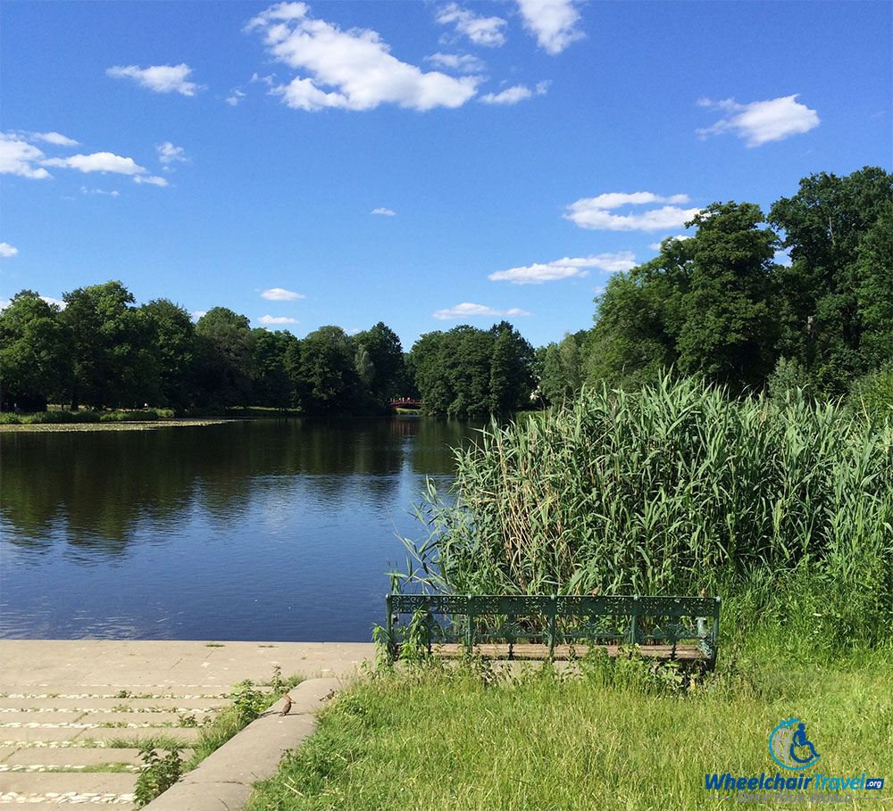 PHOTO DESCRIPTION: An empty bench surrounded by grass and weeds in front of a lake at Charlottenburg Palace.