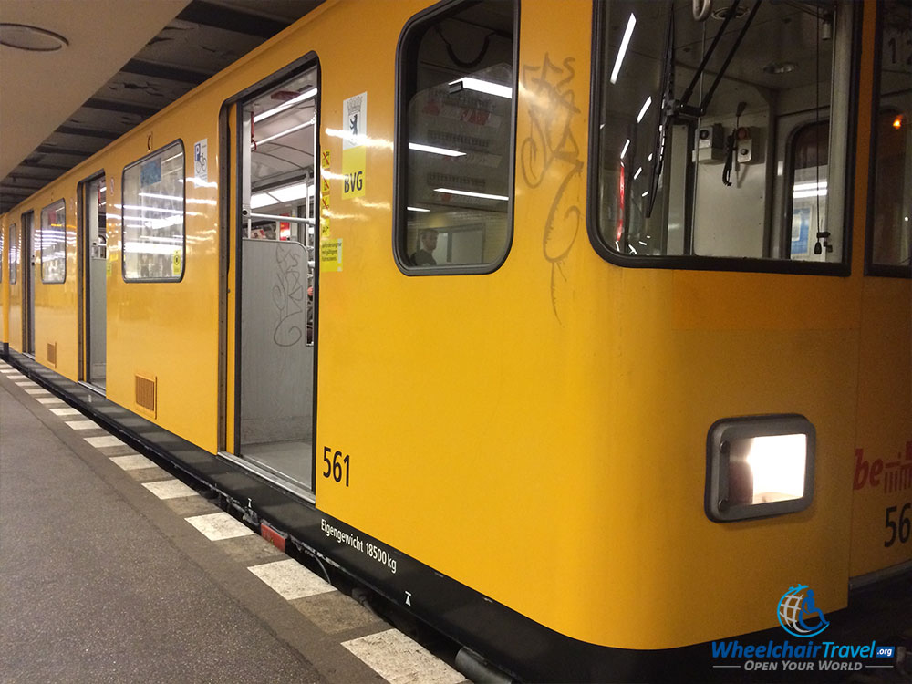 PHOTO DESCRIPTION: A yellow train on the Berlin U-Bahn system with a door entryway sitting 5-6 inches above the platform.