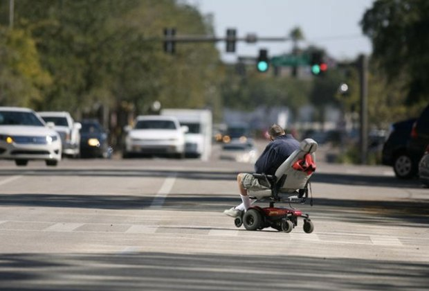 Man crossing the road in a power wheelchair