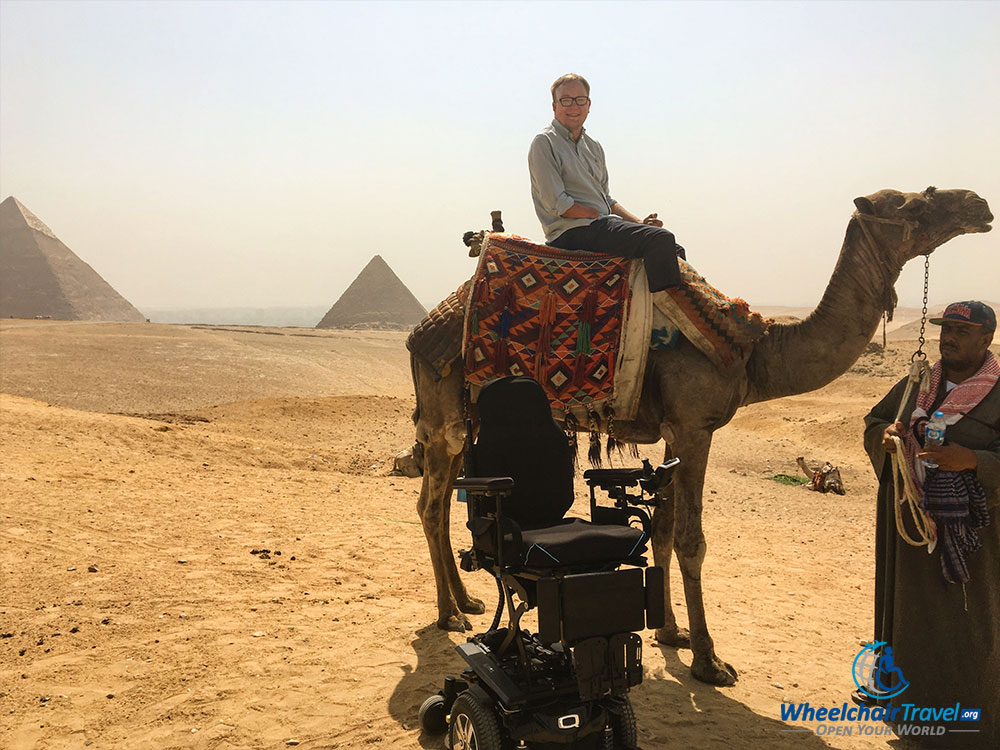 Quantum Q6 Edge 2.0 power wheelchair next to John, sitting on a camel's back.