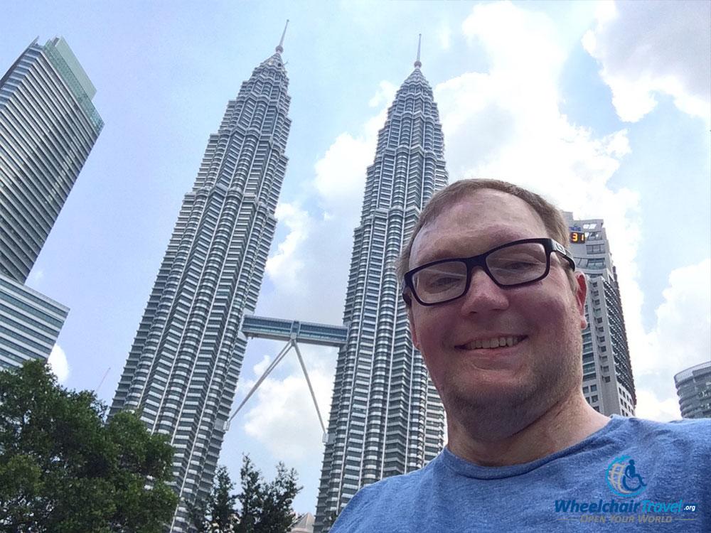 Wheelchair travel selfie with the Petronas Twin Towers in Kuala Lumpur, Malaysia.