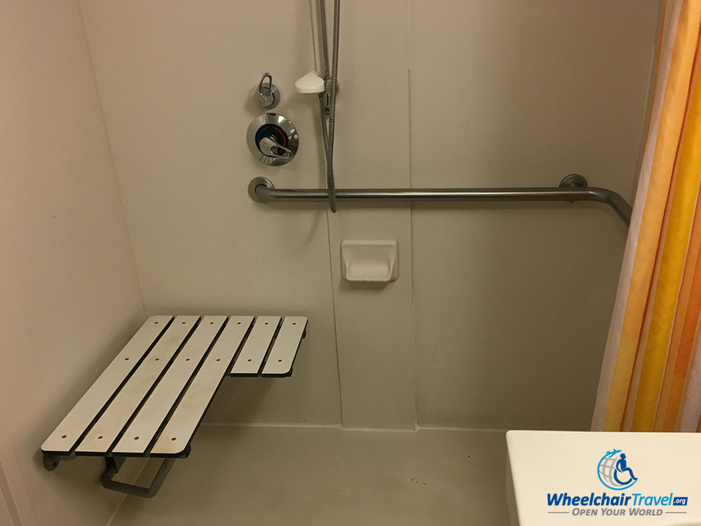 Wheelchair accessible roll-in shower with a folding seat attached to the wall.