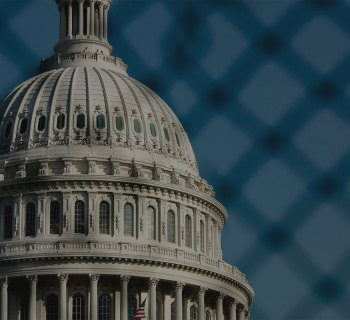 Dome of the United States Capitol Building, seen through a chain-link fence.