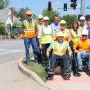 Road construction crews at a sidewalk curb cut, testing out a wheelchair.