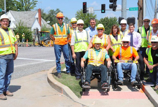 Road construction crews at a sidewalk curb cut, testing out a wheelchair.