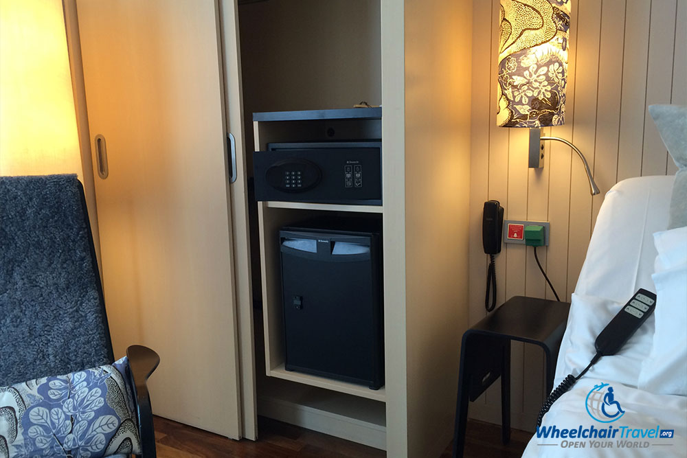 Mini fridge, safe and closet alongside the bed.
