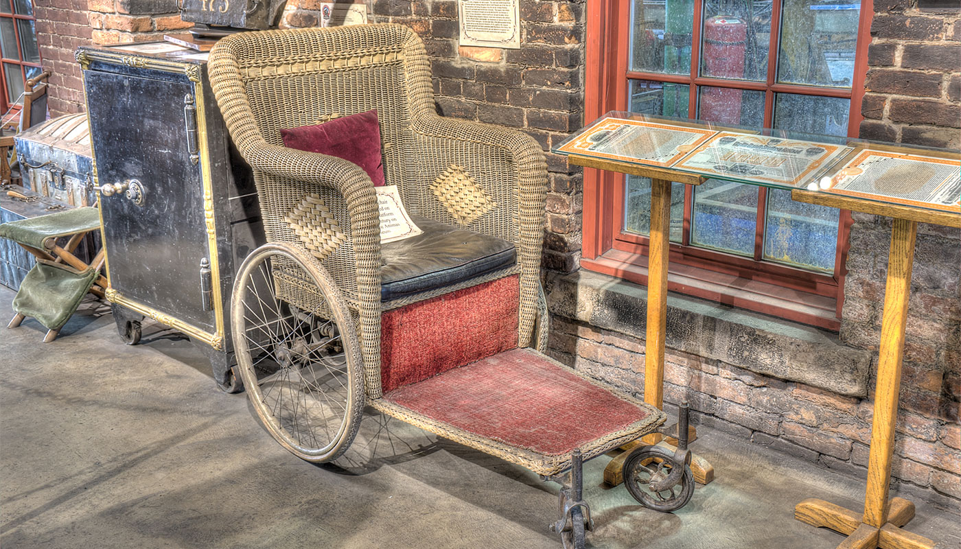 Historic wheelchair displayed in a museum.