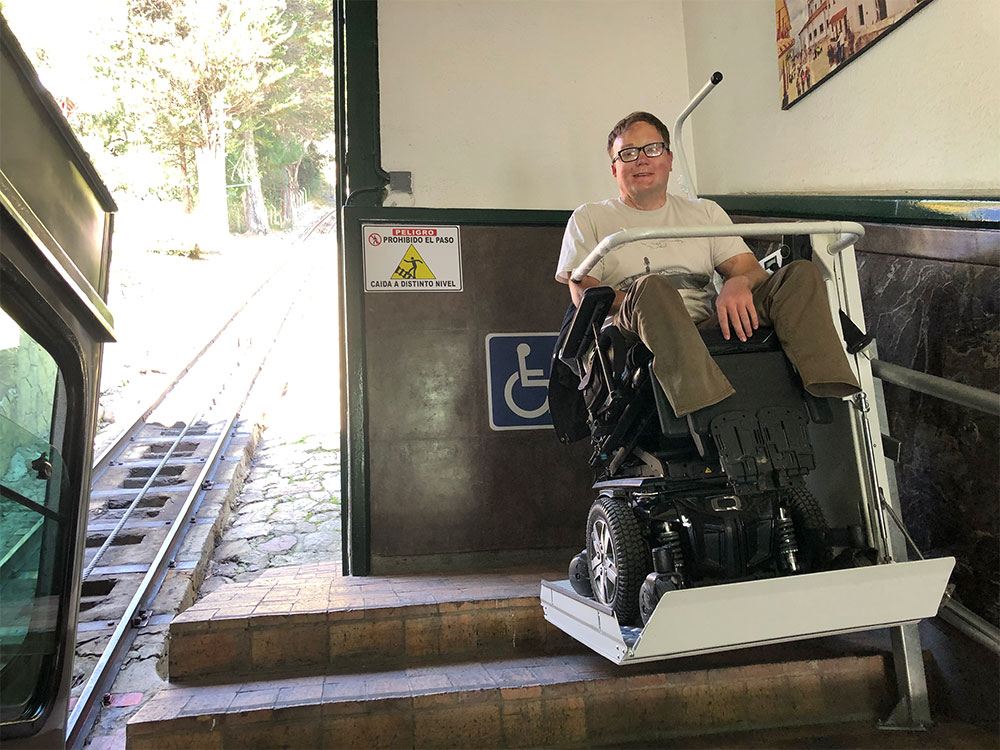 Riding the wheelchair lift to the top of the stairs.