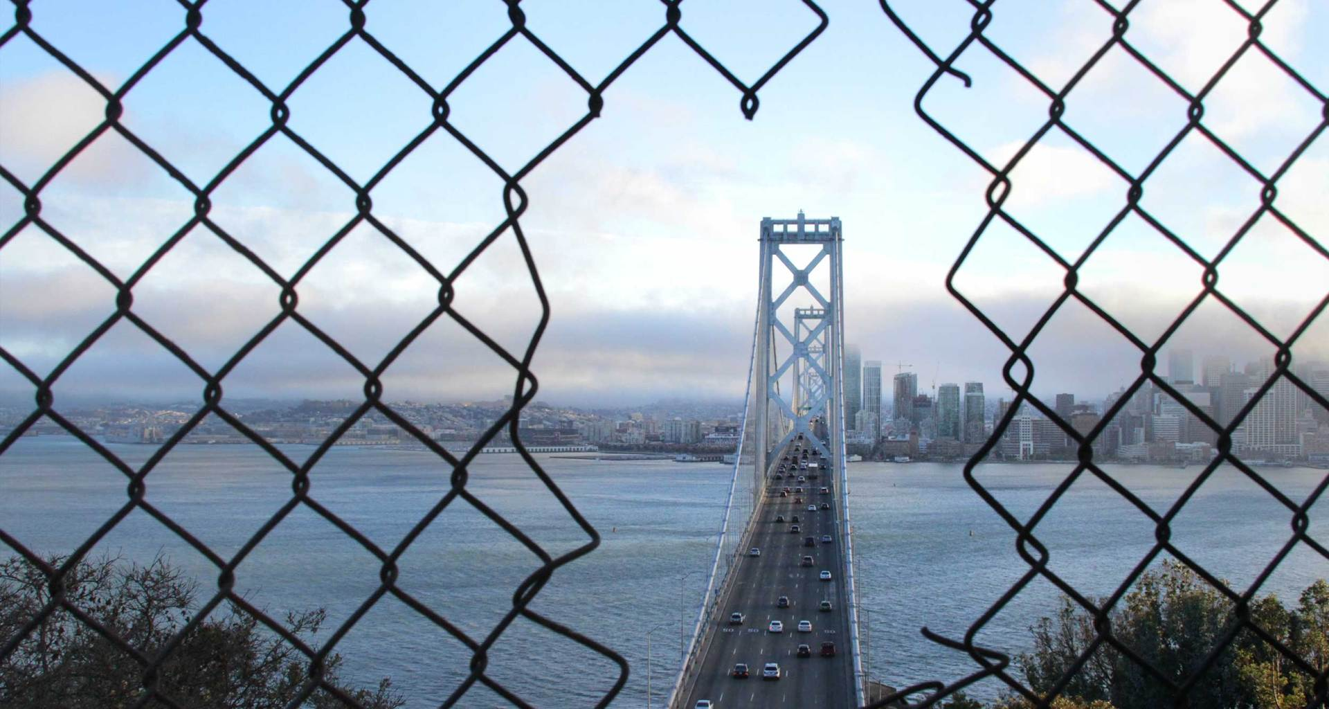 Bridge seen through wire fence.