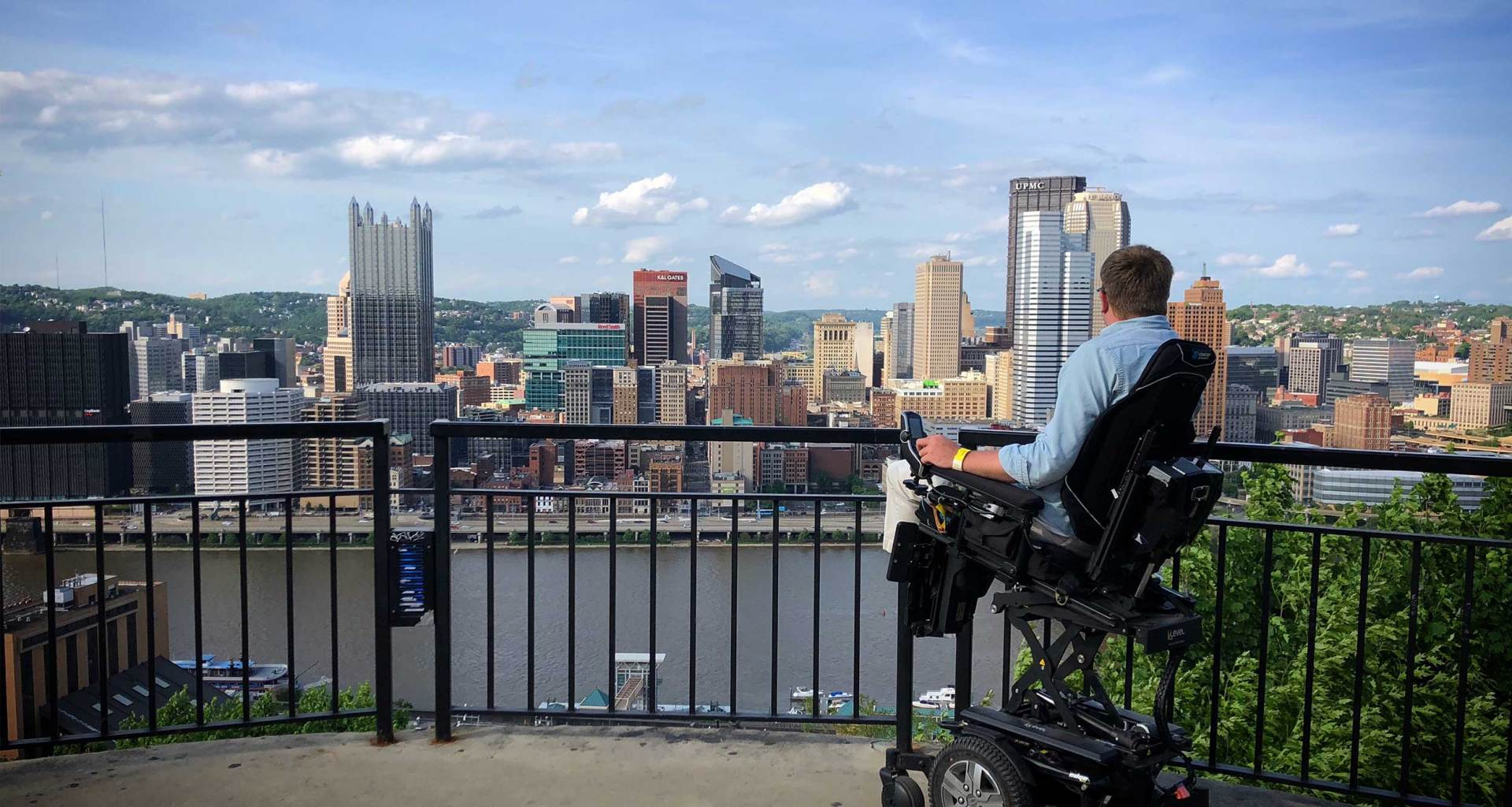 Power wheelchair in front of city skyline.