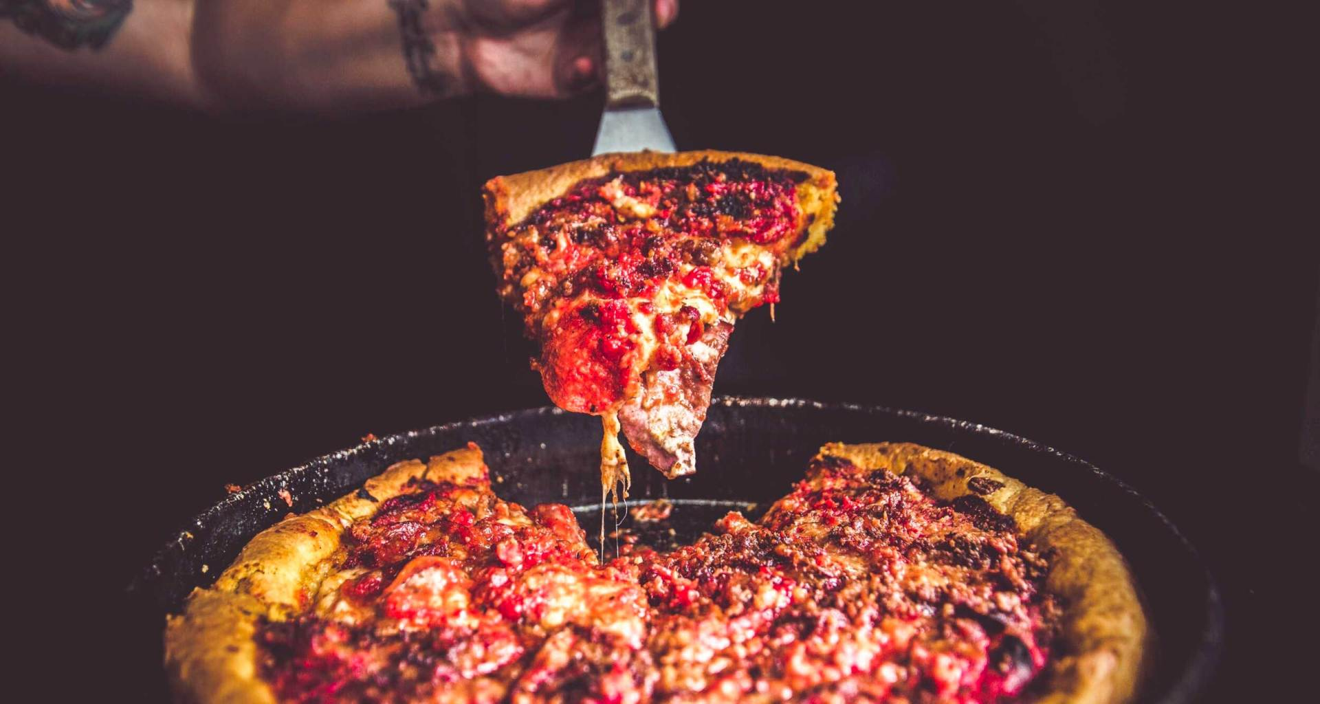 Slice of deep dish pizza being lifted from the whole pie.
