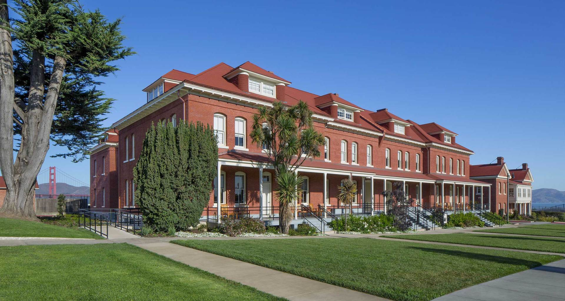 Exterior of The Lodge at the Presidio, a three story brick building sitting in front of the Golden Gate Bridge.