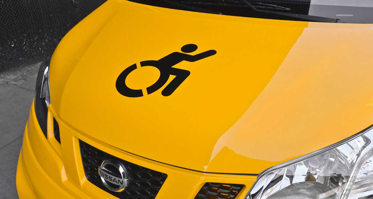 Close-up of yellow taxi van, with wheelchair emblem on hood.