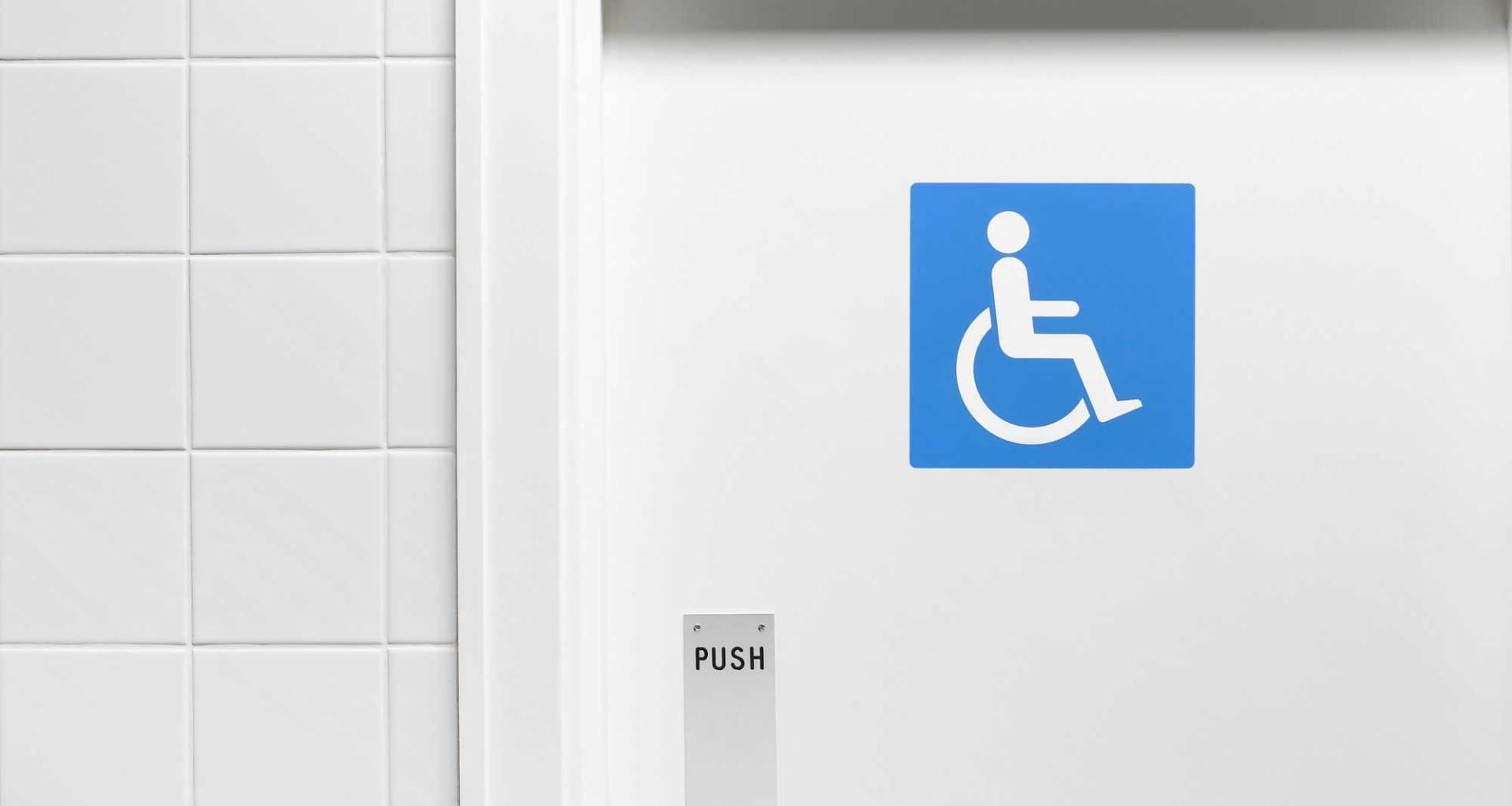 Blue wheelchair icon on white door to bathroom.
