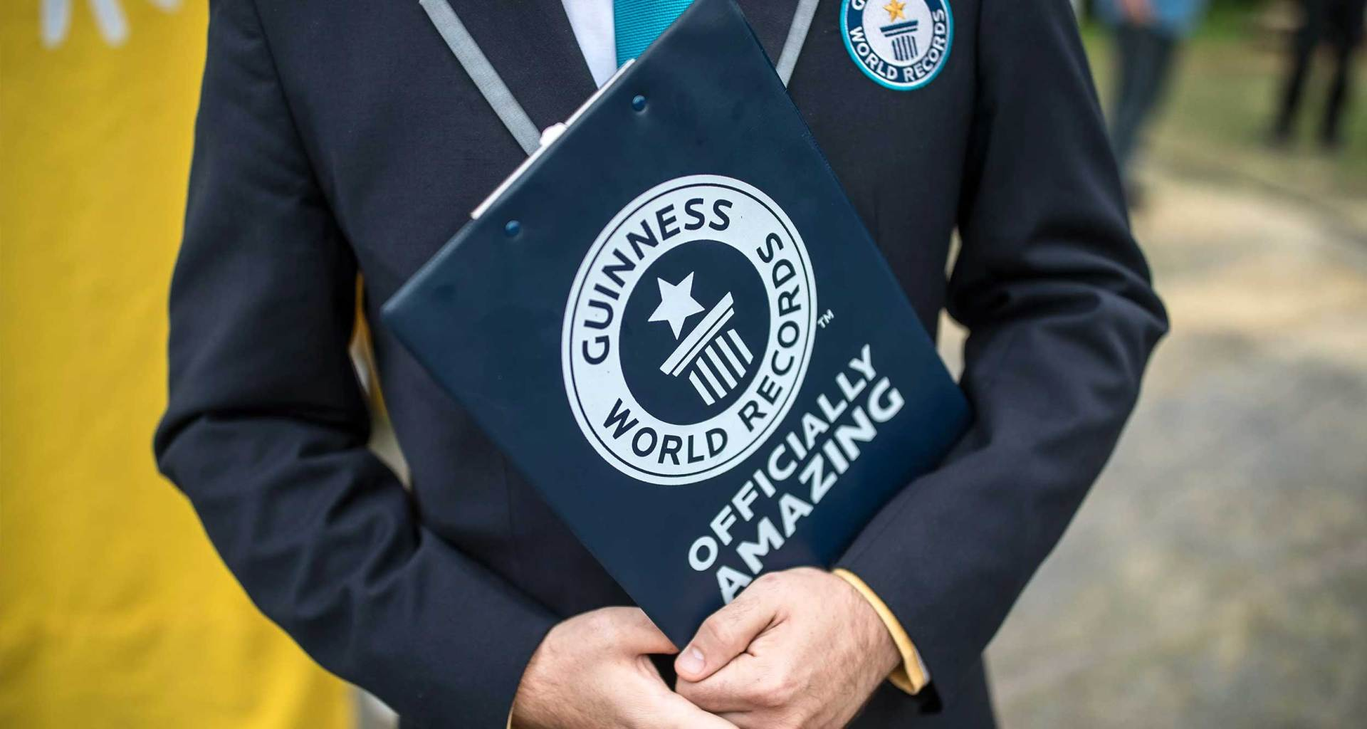 Man in suit holding folder with Guinness World Records logo.