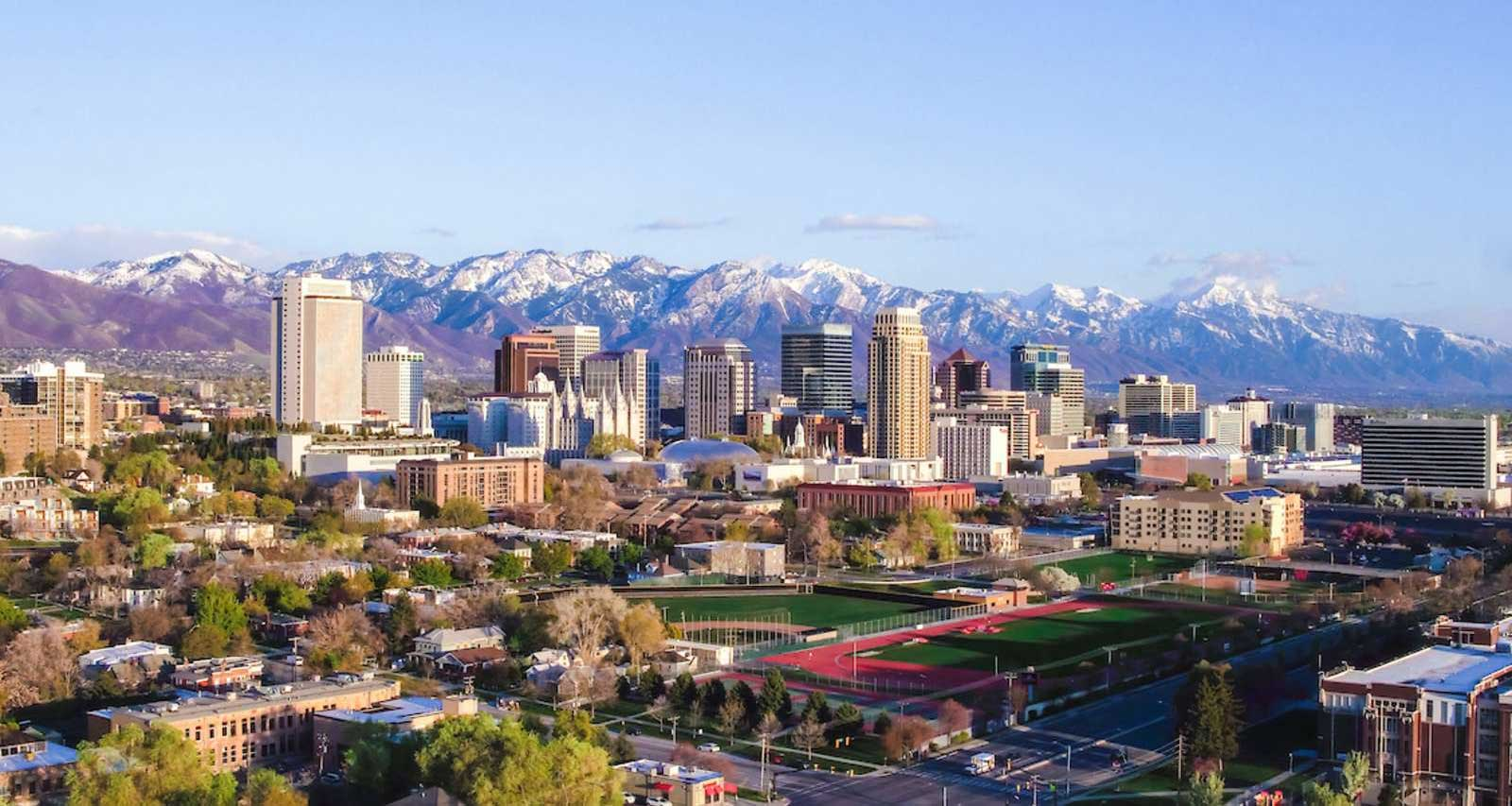 Salt Lake City skyline with snow-capped mountains in the background.