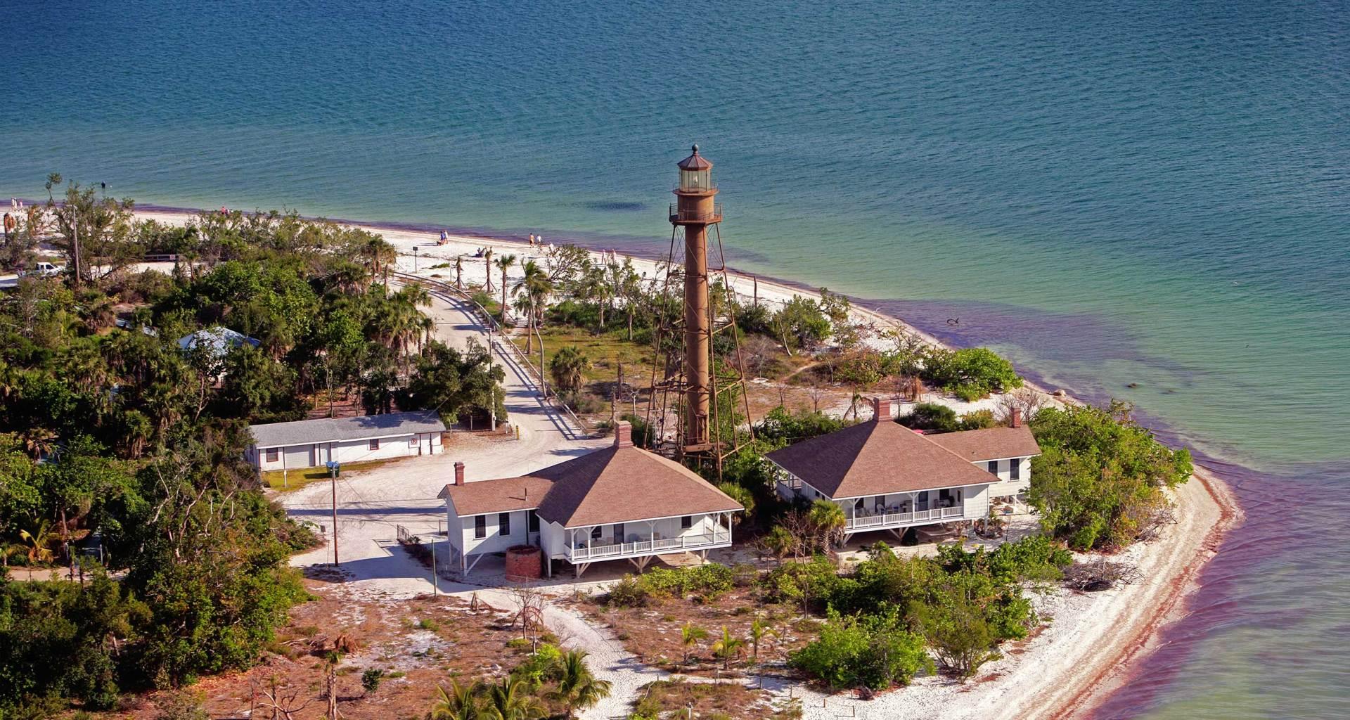 Lighthouse at edge of a beach.