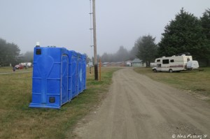 View down towards entry of dispersed camping area. Porta porties on the left. RV is parked on the right.