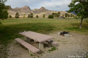 """View of typical """"sitting area"""" with picnic table and fire-pit. This is in upper loop."""