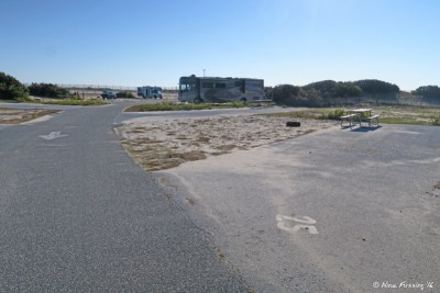 View down E loop. Empty site E25 on right with RV in E21 two sites behind it.
