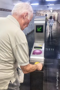 Dad inserts his ticket to pass through the turnstile