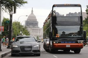 In this July 15, 2016, photo, a double decker tour bus drives by an Audi self driving vehicle parked on Pennsylvania Avenue, near the Capitol in Washington. The federal government should be in charge of regulating self-driving cars rather than states since the vehicles are essentially controlled by software, not people, Obama administration officials said Sept. 19 as they laid out the broad outlines of their plans to help get the transformational technology safely onto the nationþÄôs roadways. (AP Photo/Pablo Martinez Monsivais)
