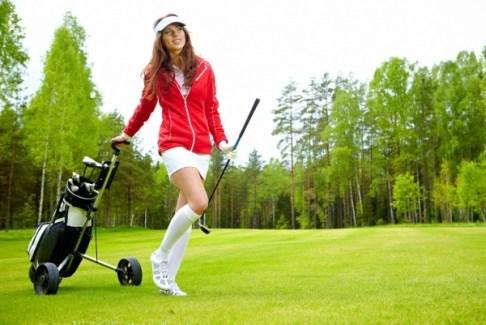 female golf player walking on fairway with their golf trolleys