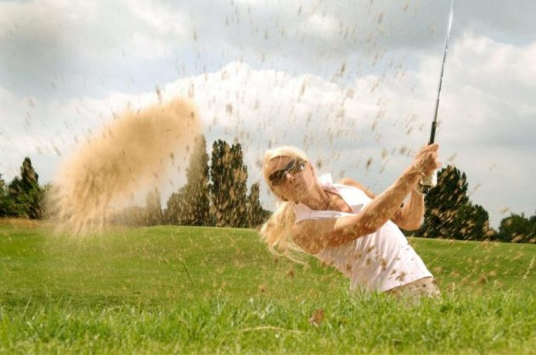 Woman playing golf to get fit without a gym