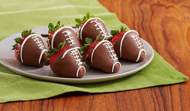 Chocolate-covered strawberries decorated like footballs