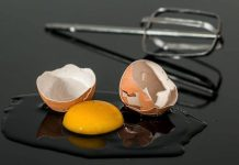 Broken eggshell with a bright yellow yolk, and a beater from a mixer lays behind it