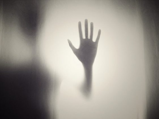 Silhouette of hand reaching up on frosted glass